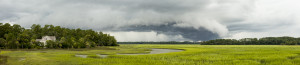 Threatening storm front moving over coastal home, wide panorama