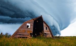 tornado forming behind old barn on american plains